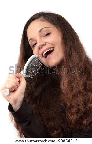 Woman singing into her hairbrush - stock photo