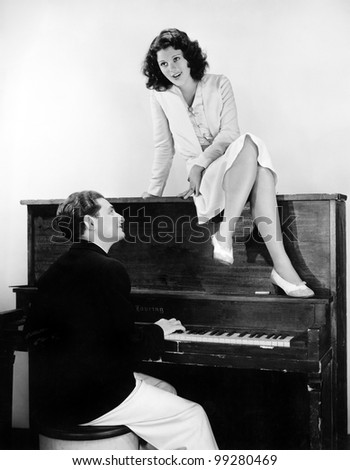Woman singing on an upright piano with a friend playing
