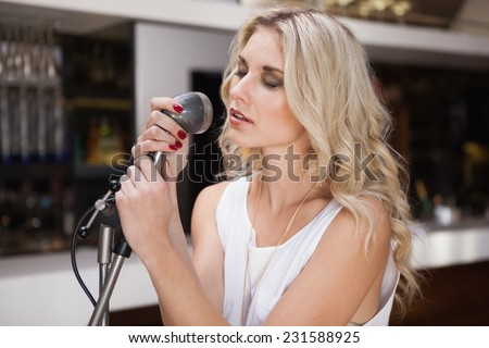 Woman singing while closing her eyes at the nightclub - stock photo