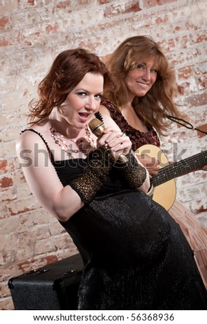 Woman sings along with guitar in front of a brick background - stock photo