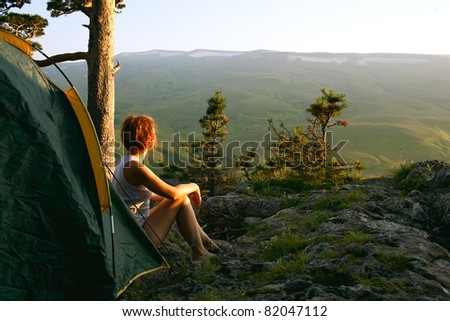 woman sit next to the tent on sunset - stock photo
