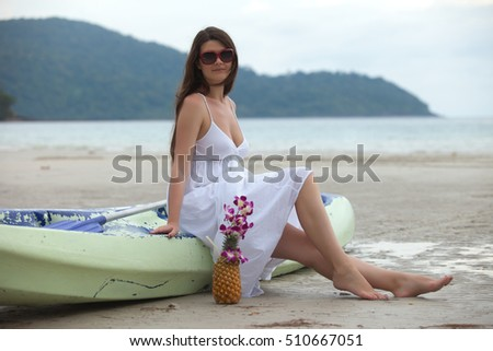 woman sit on boat on beach