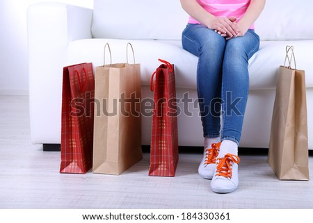 Woman sit on sofa with bags of shopping close-up - stock photo