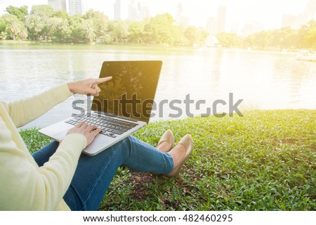 Woman sit to point silver laptop at parks and building in the city with gold light, Bangkok Thailand