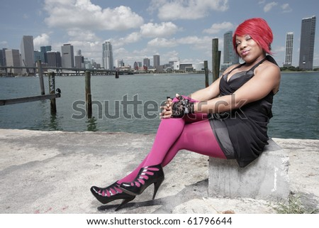 Woman siting in fashionable clothing with downtown in the background