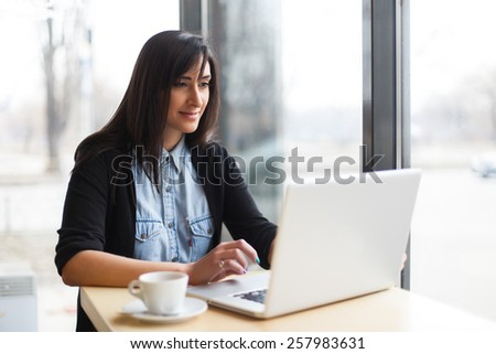 woman siting with coffee and using laptop in cafe - stock photo
