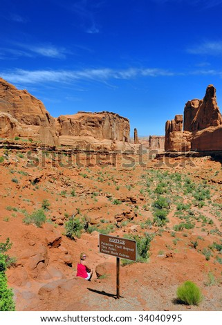 Woman Sits At Entrance to Park Avenue in Arches National Park - stock photo