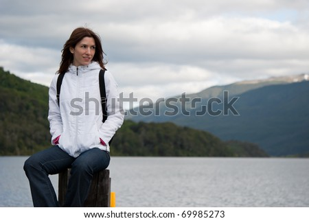 Woman sits contemplating landscape on wood pier - stock photo