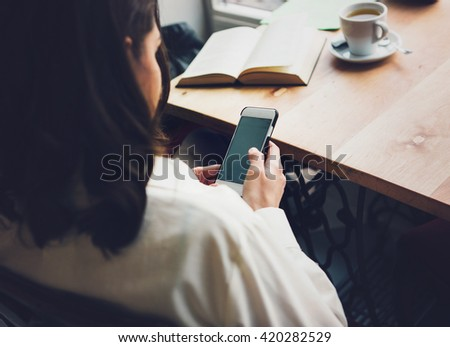 Woman sits in a cafe with a cup of coffee, tea. Read a book and dream. Looking at mobile phone. Wait for somebody.Sad woman