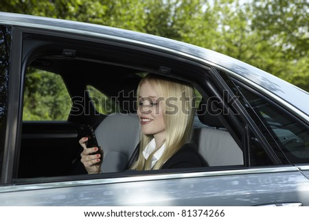 Woman sits in a car and holds her mobile phone in her hand