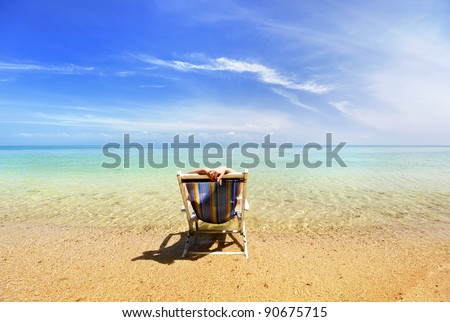 Woman sits on chair in sea sand sun