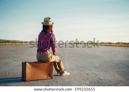 Woman sits on retro suitcase and looks away on road, theme of travel, space for text - stock photo