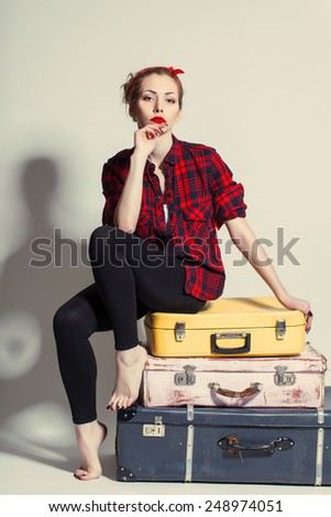 woman sits on retro suitcases - stock photo