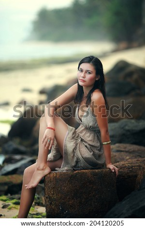 Woman sits on rocky summit above sea, looking at the camera - stock photo