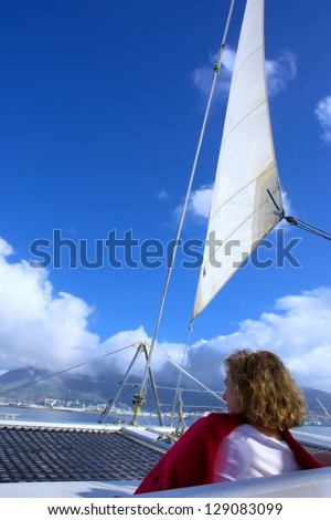 Woman sits under sail. Shot near Cape Town, Western Cape, South Africa. - stock photo