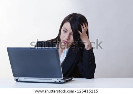woman sitting a a desk working hard on a laptop computer, deep in thought