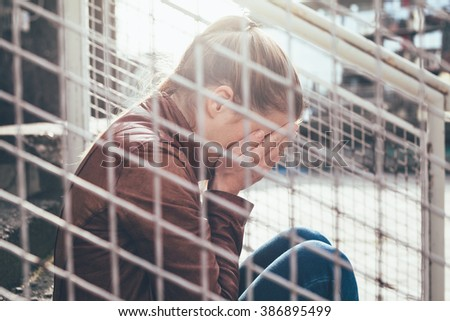 Woman sitting alone and crying - stock photo