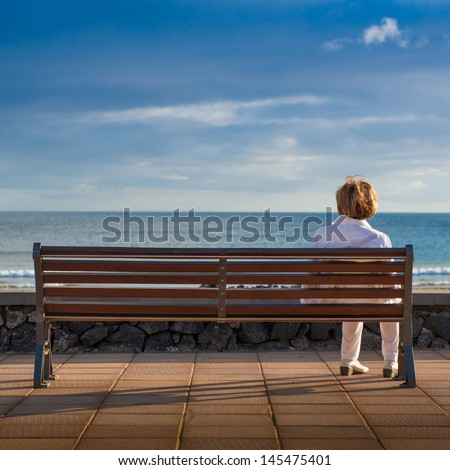 Woman sitting alone in a bench, looking at the sea