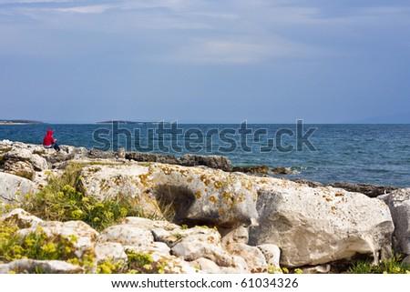Woman sitting alone on rocks on seaside in croatia - stock photo