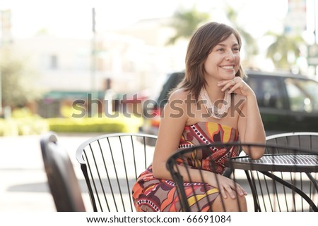 Woman sitting and smiling at a table - stock photo