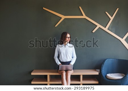 woman sitting and working in modern office interior - stock photo