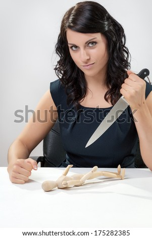 woman sitting at a desk about to stab an artist wooden figure