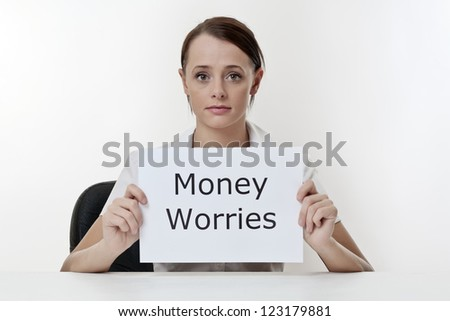woman sitting at a desk worried about her money problems - stock photo