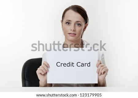 woman sitting at a desk worried her credit card - stock photo
