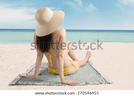 Woman sitting at beach while wearing bikini with hat, enjoying summer holiday - stock photo