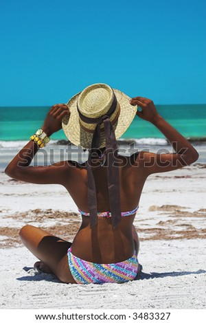 woman sitting at beach with straw hat - stock photo