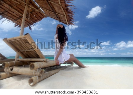 Woman sitting at chaise lounge with straw parasol on white sandy beach at Philippines - stock photo