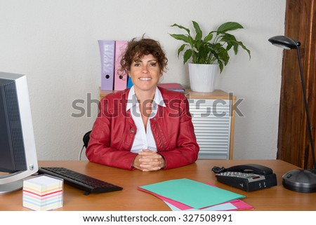 Woman sitting at desk working at office,  serious, thinking. - stock photo