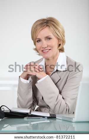 Woman sitting at her desk with laptop and open diary - stock photo