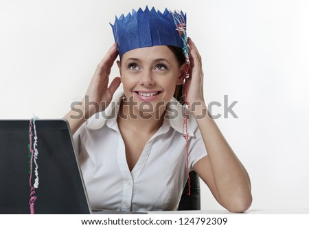 woman sitting at her desk working, wearing a paper hat from a christmas cracker having a party