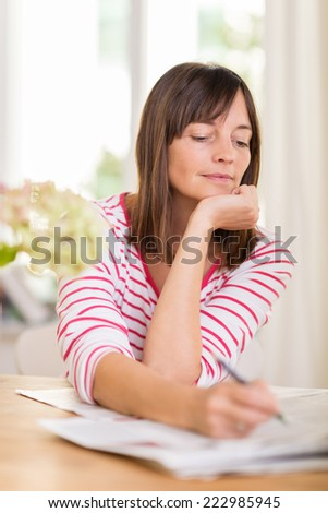 Woman sitting at her dining table doing a crossword puzzle in the local newspaper staring thoughtfully at the page with a pen in her hand - stock photo