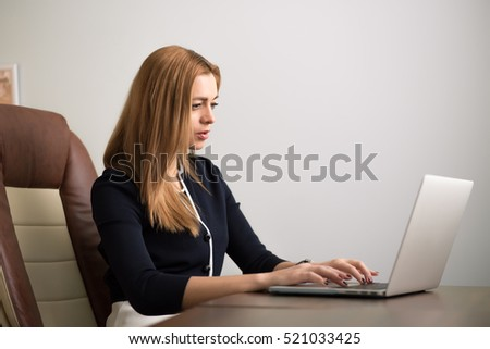 Woman sitting at her workplace in office and working by notebook