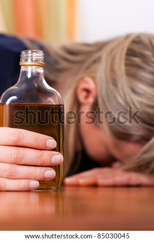 Woman sitting at home drinking way too much brandy alcohol, she is addicted - stock photo