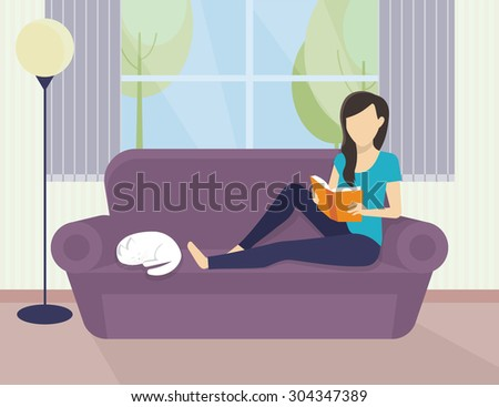 Woman sitting at home on the sofa and reading a book - stock photo