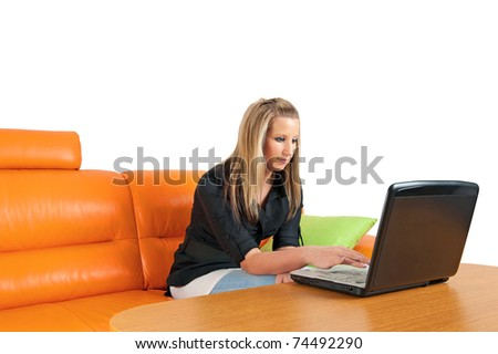 Woman sitting at home using a laptop - stock photo