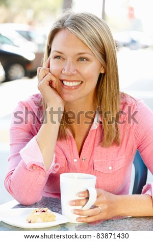 Woman sitting at sidewalk caf - stock photo