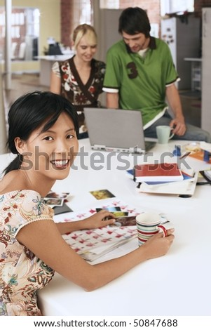 Woman sitting at table with two people using laptop in background. - stock photo