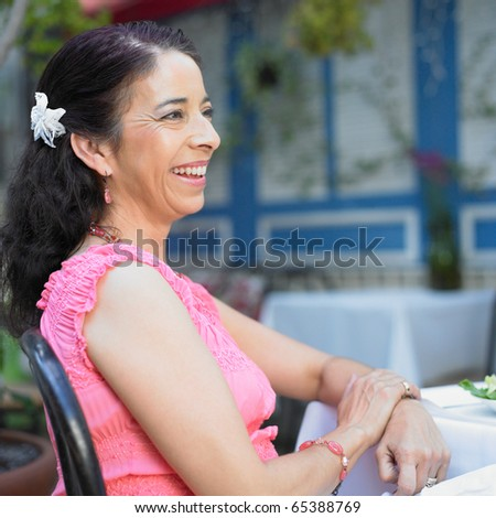 Woman sitting at the dinner table - stock photo