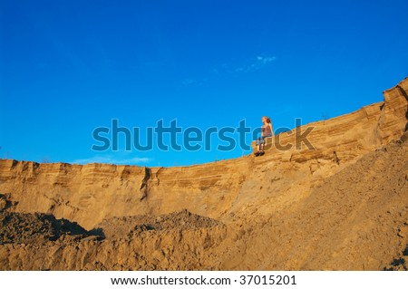 woman sitting at the edge of canyon - stock photo