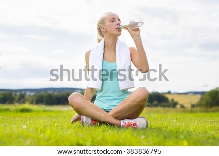 Woman sitting at the grass and drinking water after workout