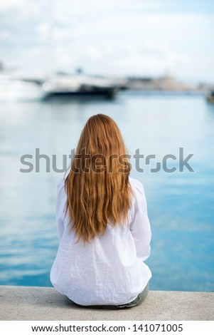 Woman sitting at the harbour on the quay with her back to the camera looking out at the moored boats, shallow dof - stock photo