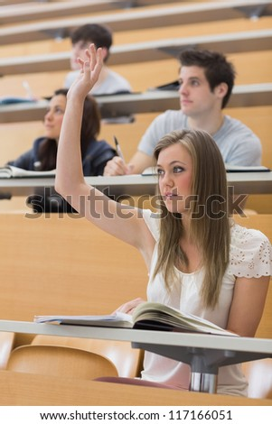 Woman sitting at the lecture hall with hand up to ask question - stock photo