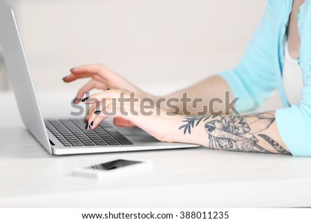 Woman sitting at the table and working with laptop - stock photo