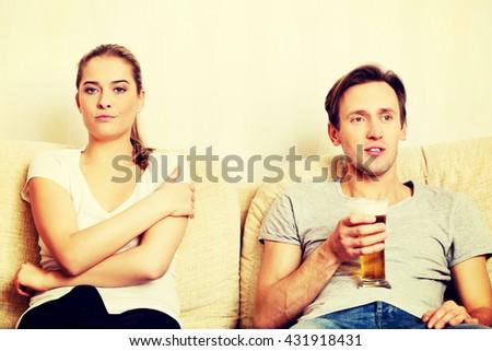 Woman sitting bored while man watching sports - stock photo