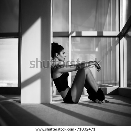 Woman sitting by a window having a rest. indoor shot - stock photo