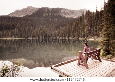 Woman Sitting by Lake - stock photo